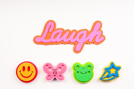 green face: The word laugh in script font of pink and orange.  Theres four foam stamps of faces, butteflly, and star.