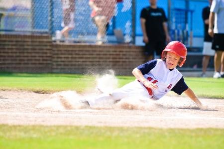 Jugador de béisbol juvenil de deslizamiento en en casa