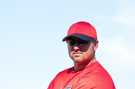 Baseball coach wearing sunglasses and looking at camera. Banco de Imagens