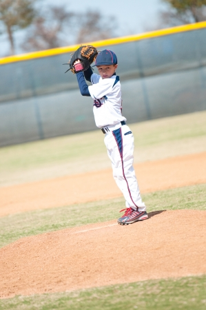 Little league pitcher starting his wind up to pitch to the ball.