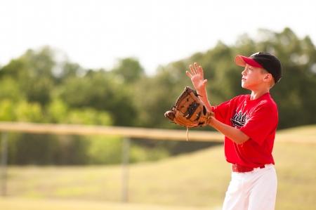 coger: Jugador de b�isbol joven en camiseta roja a punto de atrapar al vuelo pop.