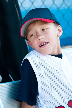 ballplayer: Little league baseball player smiling in dugout. Stock Photo