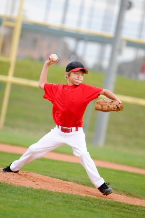 Little league pitcher in red jersey in the middle of his pitch, making a funny face.