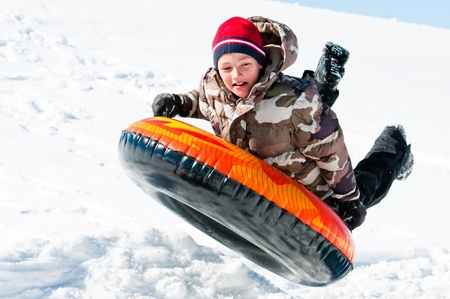 A happy boy up in the air on a tube sleding in the snow  Banco de Imagens