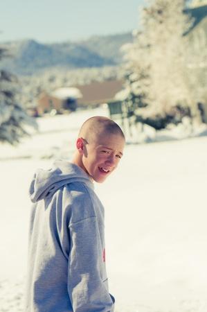 雪の中でフードを着て幸せなハゲ少年 写真素材