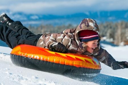 Un muchacho sonriente que se divierten sleding en un tubo en la nieve