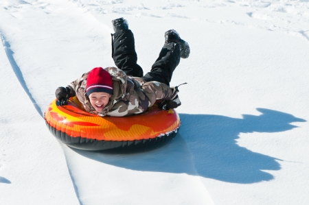 Happy boy sleding on a tube down a hill