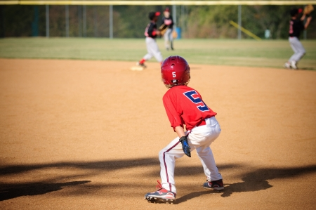Little league baseball player looking to steal second base.