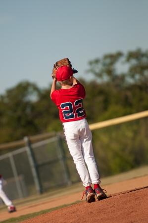 baseball pitcher: Young little league baseball pitcher checking second base runner. Stock Photo
