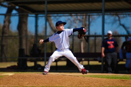 Youth baseball pitcher in wind up wearing white jersey. photo