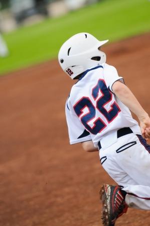 Little league baseball player running to first base. photo