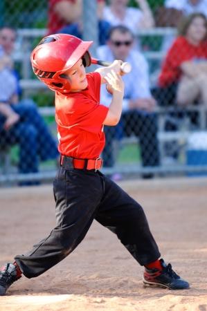 Little league baseball player full swing at bat Banco de Imagens
