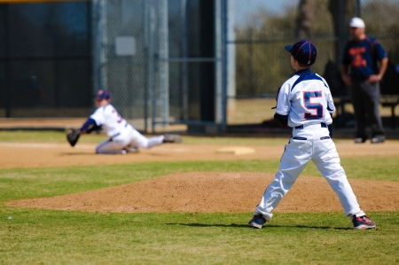 Youth baseball pitcher facing first base after the throw. photo