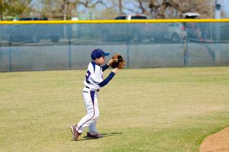 shortstop: Youth baseball shortstop about to throw the ball. Stock Photo