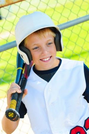 dugout: Cute baseball player smiling in the dugout about to go bat. Stock Photo