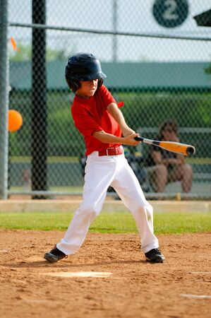 little league: Youth baseball player swinging the bat.