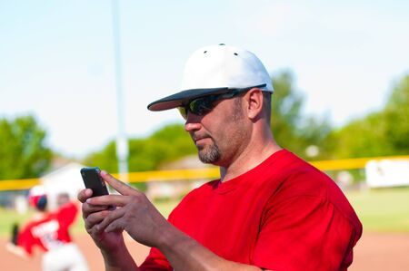 Baseball coach on cell phone during the game
