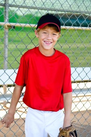baseball dugout: Jugador de Ligas Peque�as de B�isbol se inclina en la cerca dugout Foto de archivo