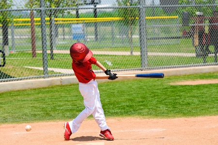Youth baseball player swinging the bat