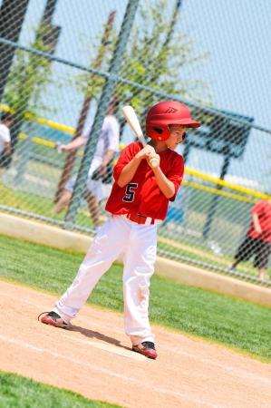 Little league baseball player in red jersey waiting to bat using a wood bat. Banco de Imagens