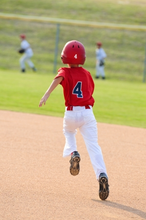 ballgame: Little league baseball boy running the bases in a game. Stock Photo