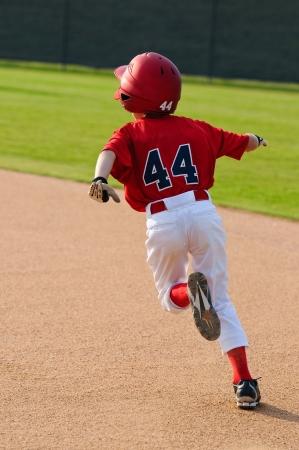 Little league baseball player running bases. Фото со стока