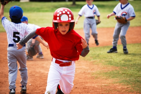 Youth little league baseball boy running bases. Stock Photo