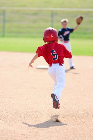 Little league boy running to second base. Stock Photo
