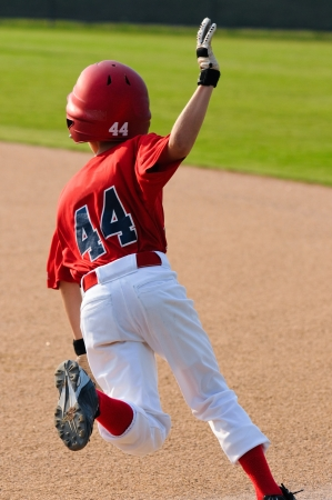 bases: Young baseball player running the bases. Stock Photo