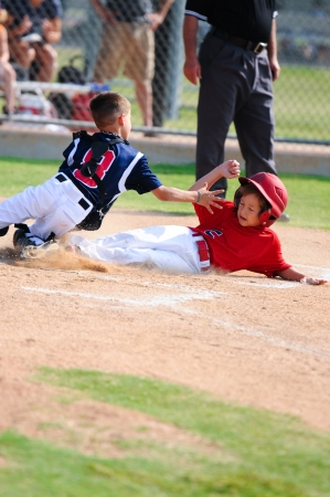 little league: Baseball boy sliding in at home plate during game. Stock Photo