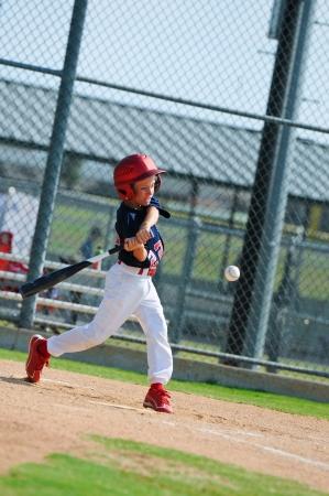 Youth baseball boy swinging the bat.