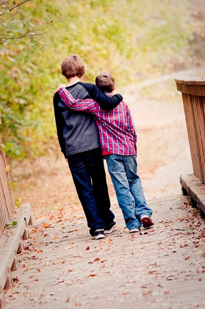 arms around: Two brothers with arms around each other walking on a bridge outdoors.