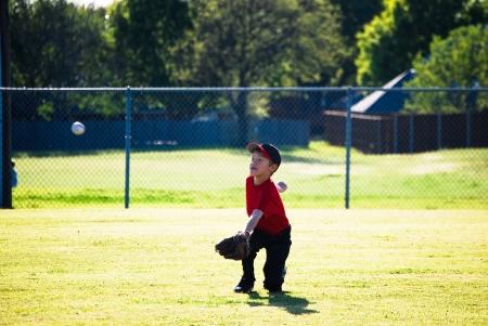 Little league baseball player diving for ball. photo