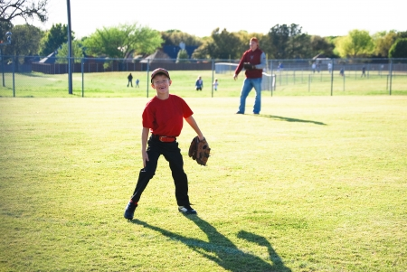 Little league baseball player laughing in outfield looking at camera. photo