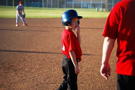 Youth baseball player looking back at coach.