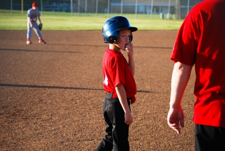 Youth baseball player looking back at coach. photo