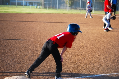 ballplayer: Youth baseball player on third base getting ready to run. Stock Photo
