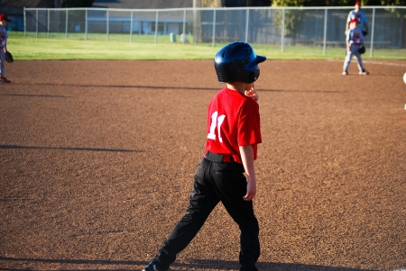 Youth baseball player on third base getting ready to run. photo