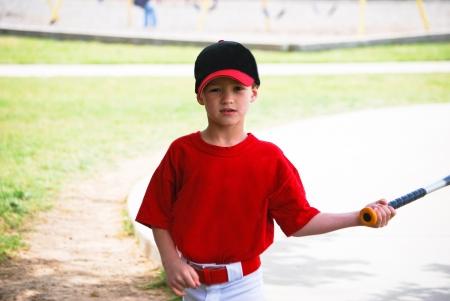 Youth baseball boy holding bat looking at camera. photo