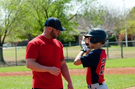 Baseball coach giving instruction to teen baseball boy. Stock Photo