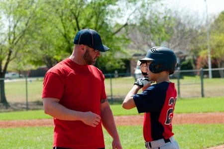 Coche de béisbol dando instrucción a boy de béisbol juvenil. Foto de archivo