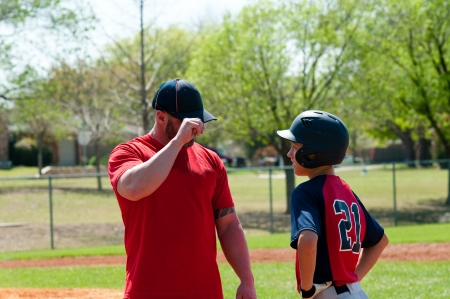Baseball coach giving signals to teen player