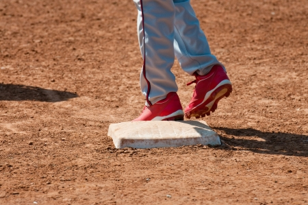 Lower body shot of a teen baseball player standing on base. photo