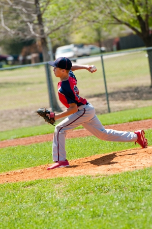 Teen baseball pitcher in the middle of throw photo