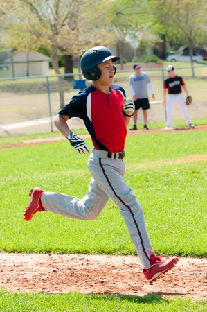 Teen baseball boy running to base. photo