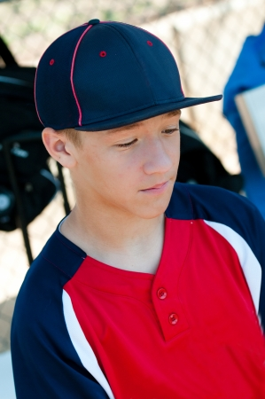 baseball dugout: Teen baseball player looking sad in dugout. Stock Photo