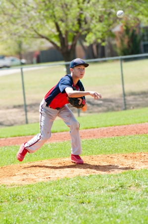 ballplayer: Teen baseball pitcher after the throw to the batter with the ball in the air.