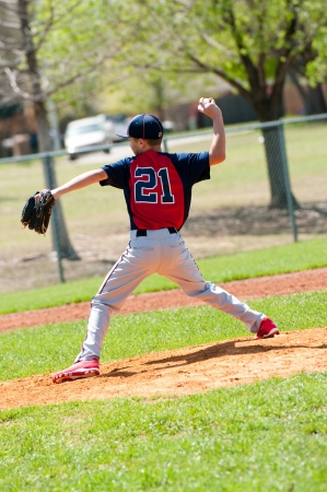 baseball pitcher: Teen baseball boy pitcher in the middle of a pitch. Stock Photo