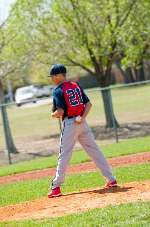 Teen baseball pitcher looking at the batter. photo