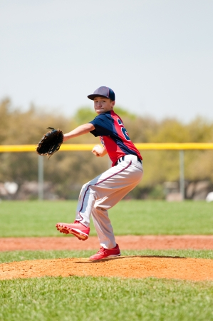 youth sports: Teen baseball player throwing a pitch.